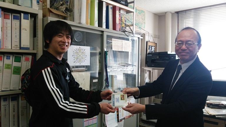 桑島君が理工学部長の多田先生にDVDを贈呈しました